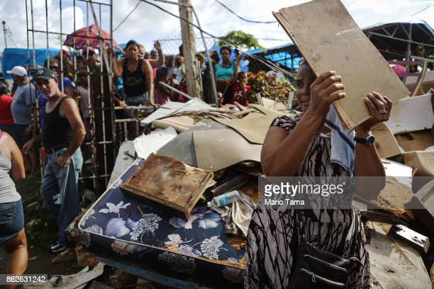A woman shields her face from the sun with a piece of wood as residents wait to receive food and water provided by FEMA in a neighborhood without...