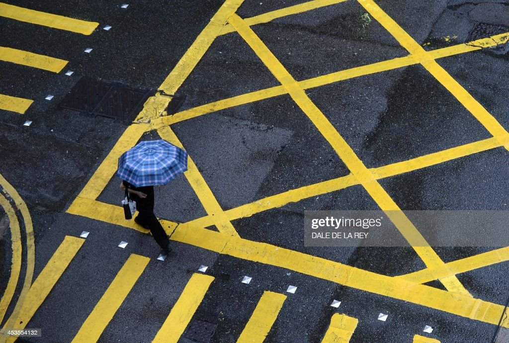A woman shields herself from the rain with an umbrella as she crosses an intersection in Hong Kong on August 13, 2014. An active southwesterly airstream associated with a trough of low pressure is bringing thundery showers to the south China coast, the Hong Kong weather observatory reported. AFP PHOTO / DALE DE LA REY