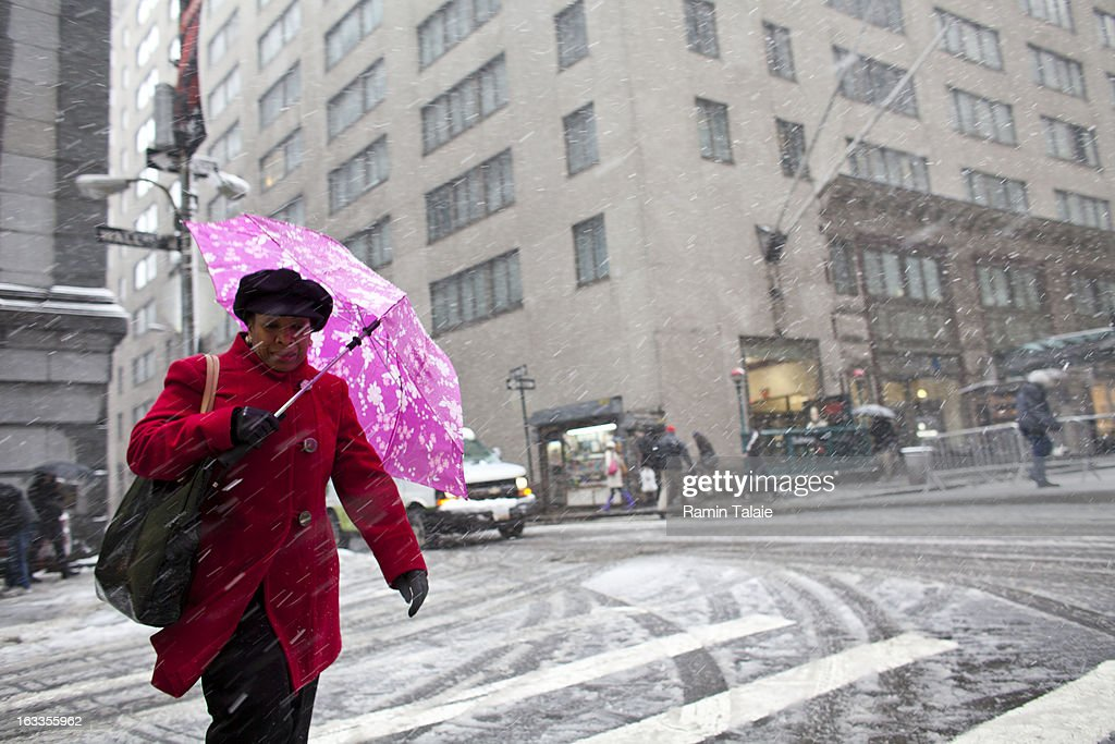 A woman shields herself from the wet snow on Wall Street on March 8, 2012 in New York City. The storm part of the same system that pummeled the Midwest is expected to dump one to two inches of snow in the New York Metro area.