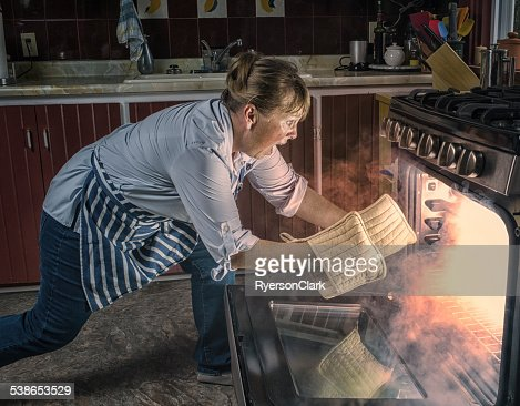 Woman  Shocked  at Oven Fire While Cooking in the Kitchen.