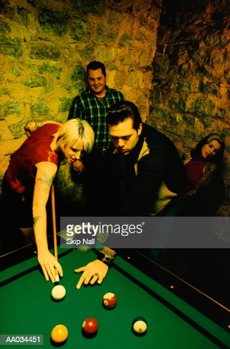 Woman Shooting Pool with Friends : Stock Photo