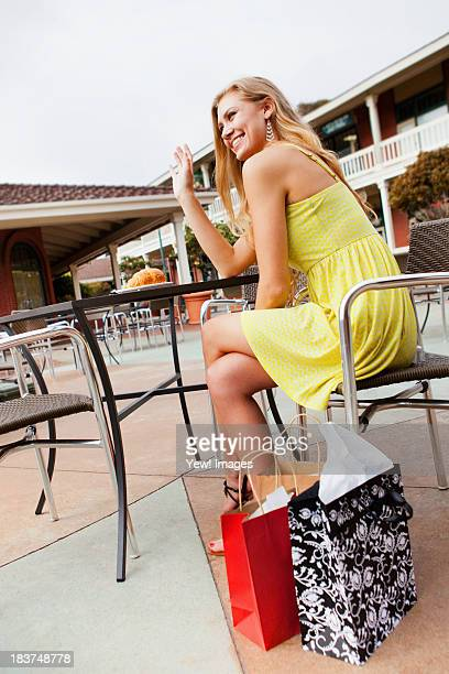 Woman shopper waving from caf?