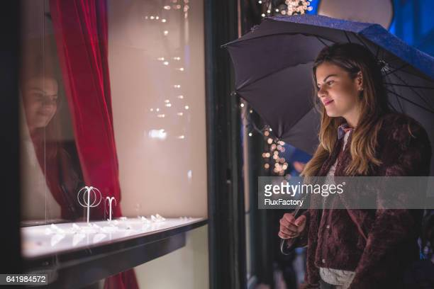 Woman shopping a jeweler on a rainy shiny night