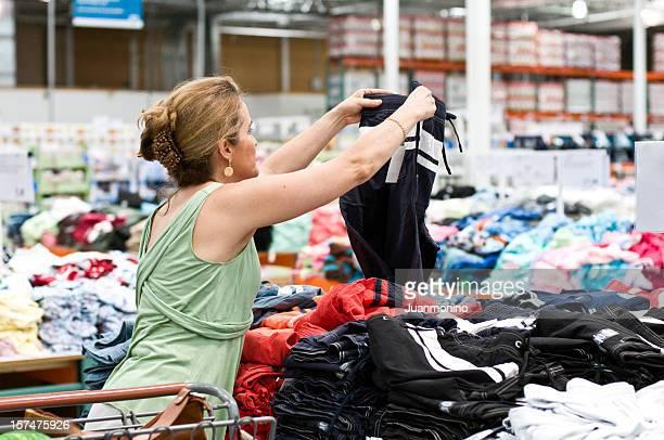 Donna shopping per abiti in un negozio di tipo di avviamento.