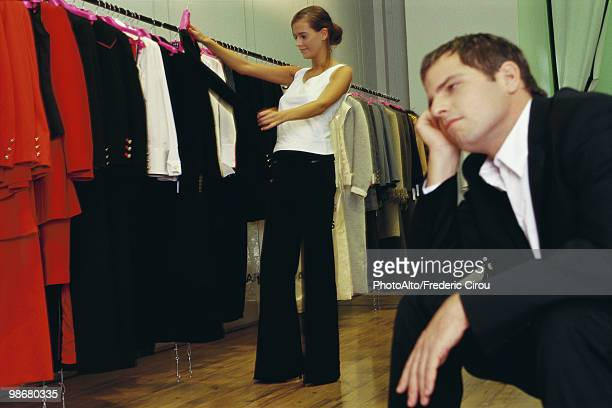 Woman shopping for clothes, bored man waiting in foreground