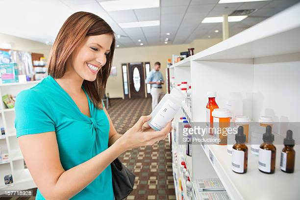 Woman shopping for medications in pharmacy/ reading labels