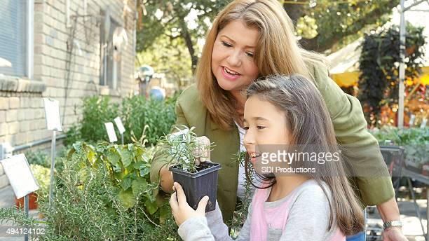 Frau shopping für Pflanzen mit Kind im Grundschulalter Tochter