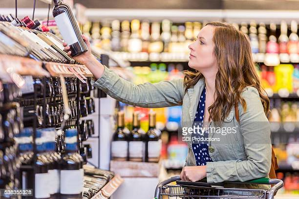 Woman shopping for red wine