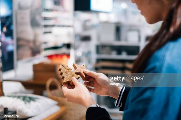 Woman shopping for wooden Christmas ornaments in shop