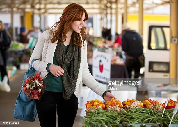Donna Shopping per giallo maturi in un mercato degli agricoltori.