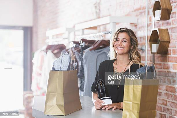 Woman shopping in clothing store paying with credit card