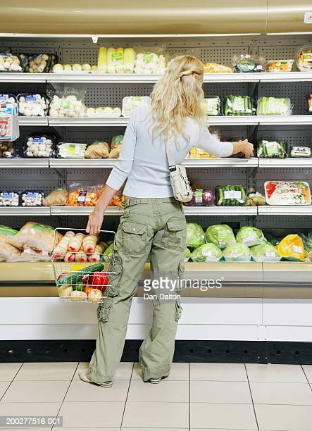 Woman shopping in produce aisle of supermarket, rear view