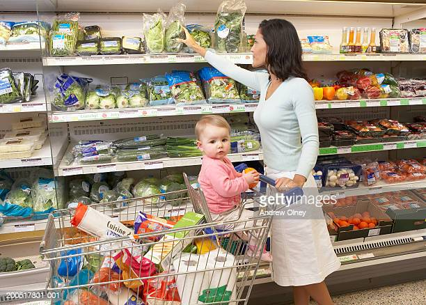 Woman shopping in supermarket, baby girl (9-11 months) in trolley