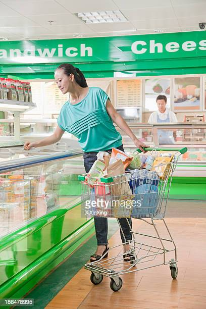 Woman shopping in supermarket, looking down in refrigerated section, Beijing