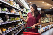 Young woman shopping in grocery store. Mature woman checking food label in supermarket. Latin woman holding shopping basket and choose a product in supermarket.