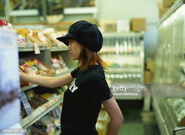 Woman shopping in supermarket, side view