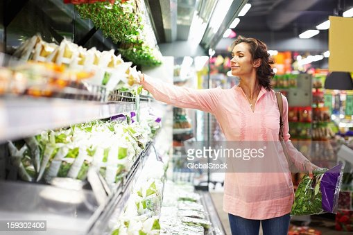 Woman shopping in the produce section of the market : Stock Photo