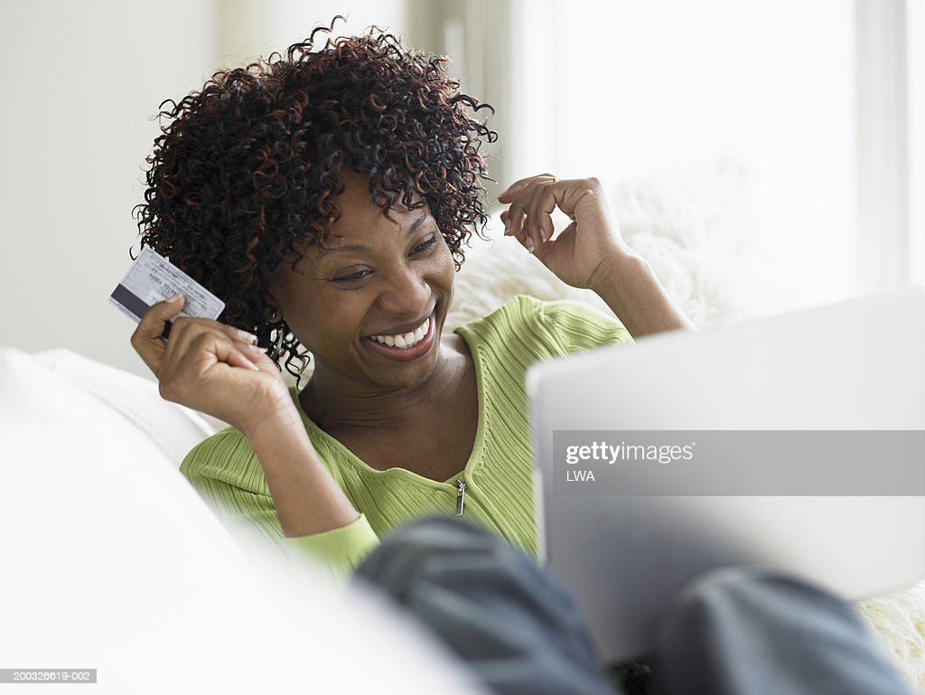 Woman shopping online, holding credit card : Stock Photo