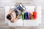 High Angle View Of Young Woman Shopping Online With Credit Card On Laptop