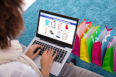 Woman Shopping Online On Laptop With Multi Colored Shopping Bags On Carpet