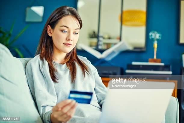 Woman shopping online with credit card through laptop at home