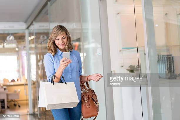 Woman shopping texting at the mall