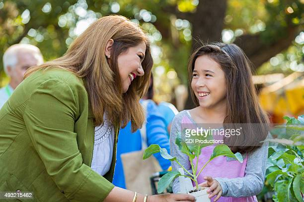 Woman shopping with little girl at gardening store or nursery