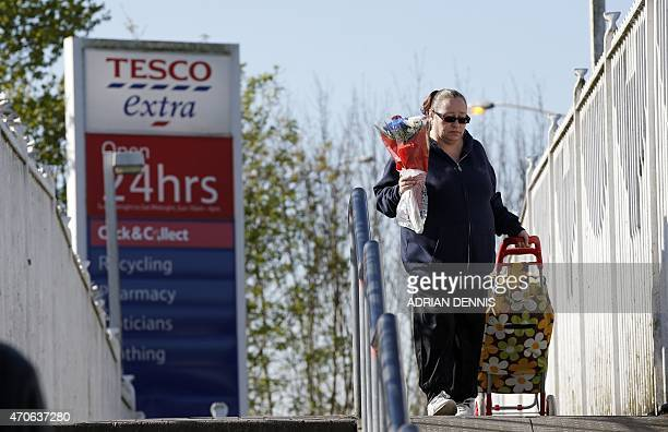 A woman shops at a Tesco supermarket in Sunbury west of London on April 22 2015 Britain's biggest retailer supermarket group Tesco announced...