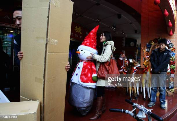 A woman shops for Christmas at a market on December 19 2008 in Beijing China A large number of Christmas decorations destined to the Western market...