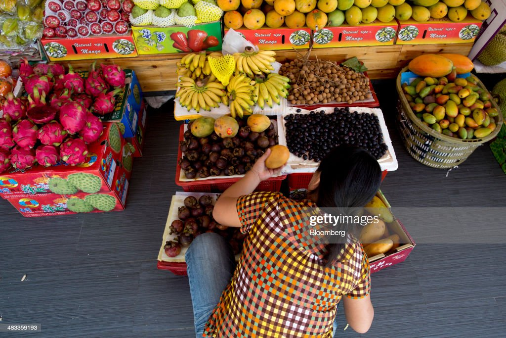 A woman shops for fruit at a stall in the Dadonghai district of Sanya, Hainan Province, China, on Monday, April 7, 2014. The yuan is poised to recover from declines that have made it Asia's worst-performing currency as China seeks to prevent an exodus of capital that would threaten economic growth, according to the most accurate forecasters. Photographer: Brent Lewin/Bloomberg via Getty Images
