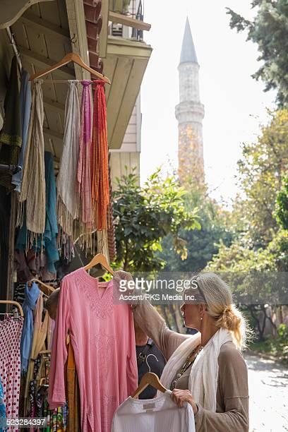 Woman shops for local textiles along lane