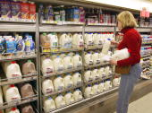 A woman shops for milk in a grocery April 12 2004 in Chicago Illinois Agriculture experts say consumers could pay as much as 50 cents more per gallon...