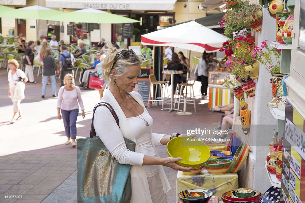 Woman shops for pottery in outdoor market : Stock Photo