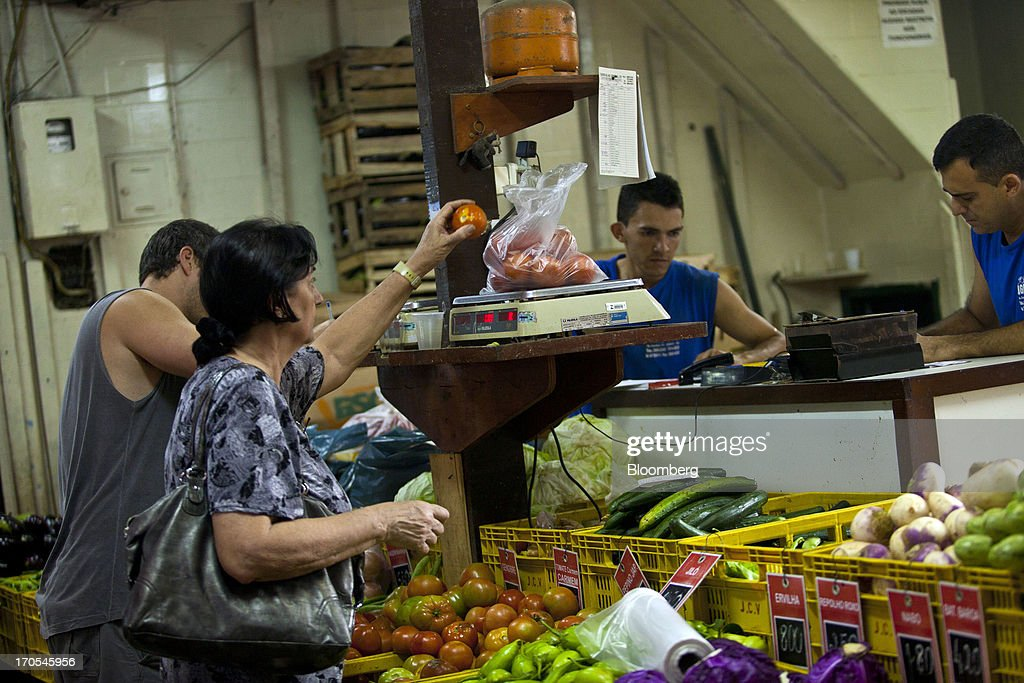 A woman shops for tomatoes at a market in Rio de Janeiro, Brazil, on Thursday, June 13, 2013. Brazilian retail sales rose in April at less than half the pace economists forecast as inflation erodes purchasing power, complicating the governments effort to boost growth. Photographer: Dado Galdieri/Bloomberg via Getty Images
