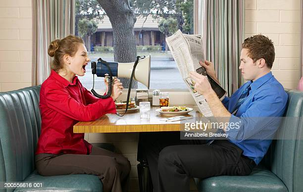 Woman shouting at man through megaphone in diner