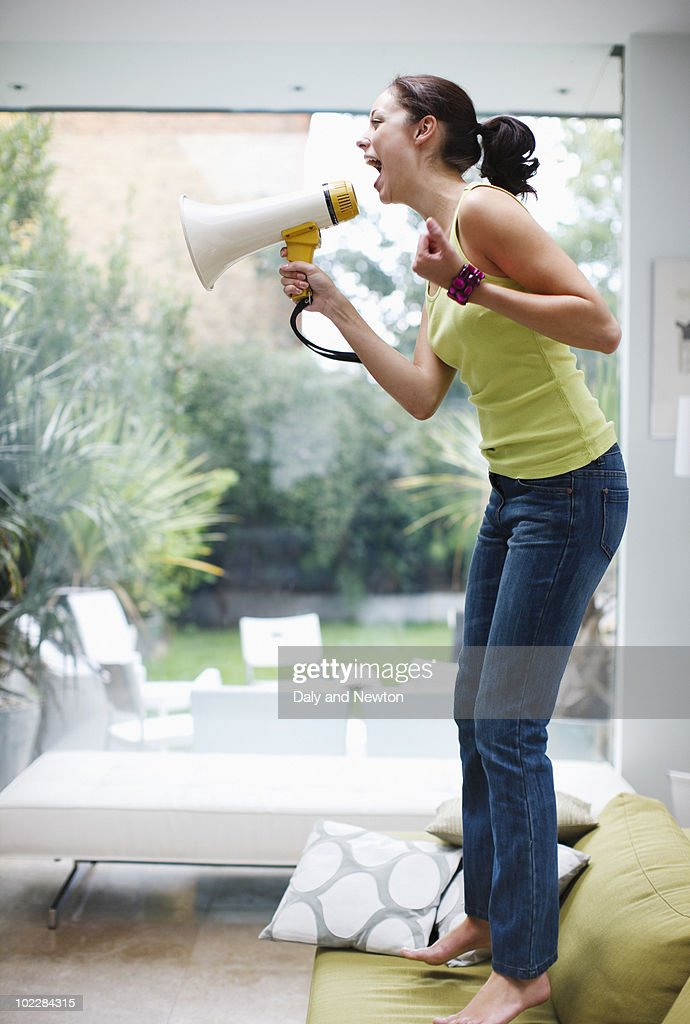 Woman shouting into bullhorn in living room : Stock Photo