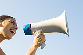Woman shouting into megaphone, low angle view, cropped
