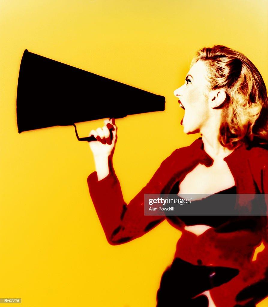 Woman shouting into megaphone, profile, yellow background : Stock Photo