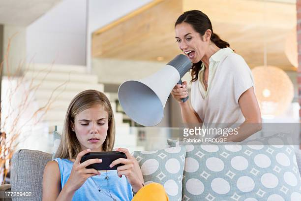 Woman shouting through a megaphone at his daughter for playing video game