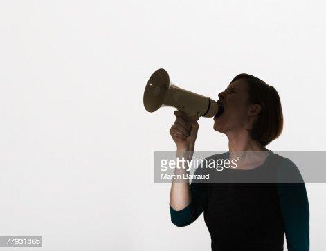 Woman shouting through a megaphone : Stock Photo