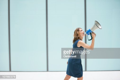 Woman shouting through megaphone at office lobby : Stock Photo