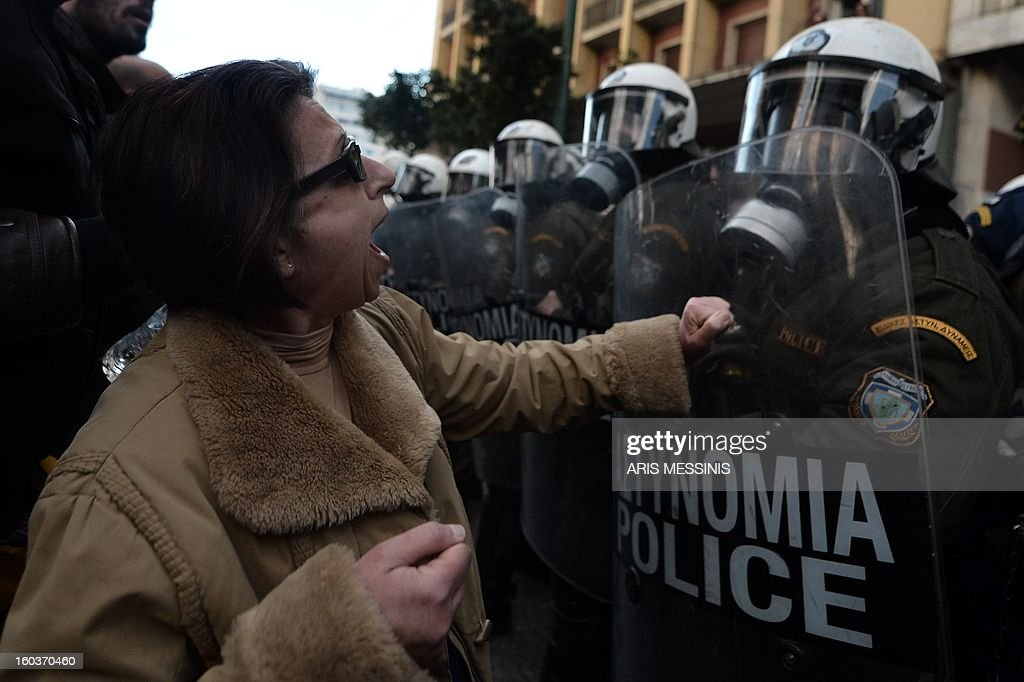 A woman shouts against riot police outside the Labour Ministry in Athens on January 30, 2013. Police were called in on Wednesday to dislodge around 30 Communist unionists from the labour ministry in a protest against new pension cut plans. The unionists were arrested and police used tear gas outside the building to disperse a larger group of protesters demanding their release. AFP PHOTO / ARIS MESSINIS