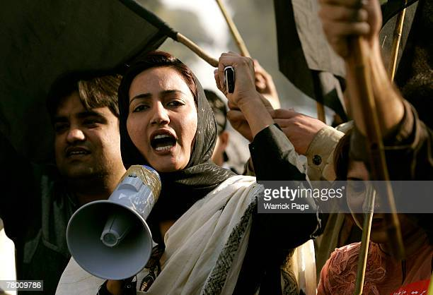 A woman shouts antigovernment slogans into a megaphone during a protest by journalists against media restrictions outside the Islamabad Press Club on...
