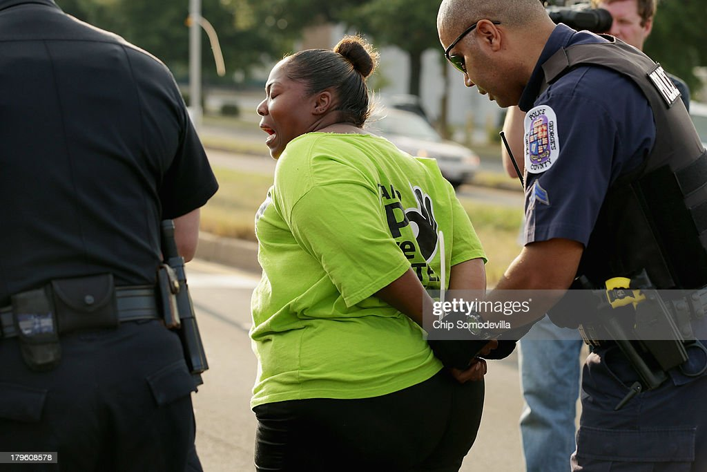 A woman shouts as she is arrested after she and hundreds of other demonstrators blocked traffic in a major intersection outside a Walmart store during rush hour September 5, 2013 in Hyattsville, Maryland. Six women were arrested during the demonstration where about 225 people gathered outside the Walmart store to protest the retail giant's labor practices. A showdown continues between Walmart and the neighboring District of Columbia, where Mayor Vincent Gray could sign a bill that would make large retailers to pay their employees a 50 percent premium over the city's minimum wage.
