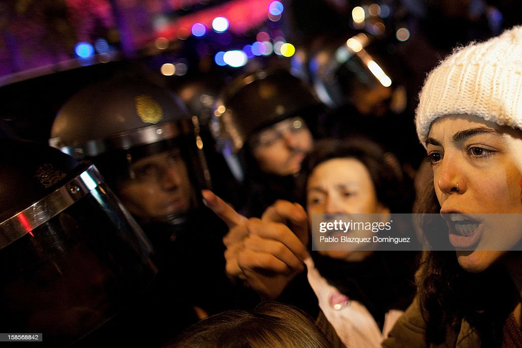 A woman shouts at riot police amid other health workers during a demonstration outside Madrid Regional Asembly on December 19, 2012 in Madrid, Spain. As of today, health workers unions are calling for a third 48-hour strike against cuts on public health care and the privatization of medical centers and hospitals.