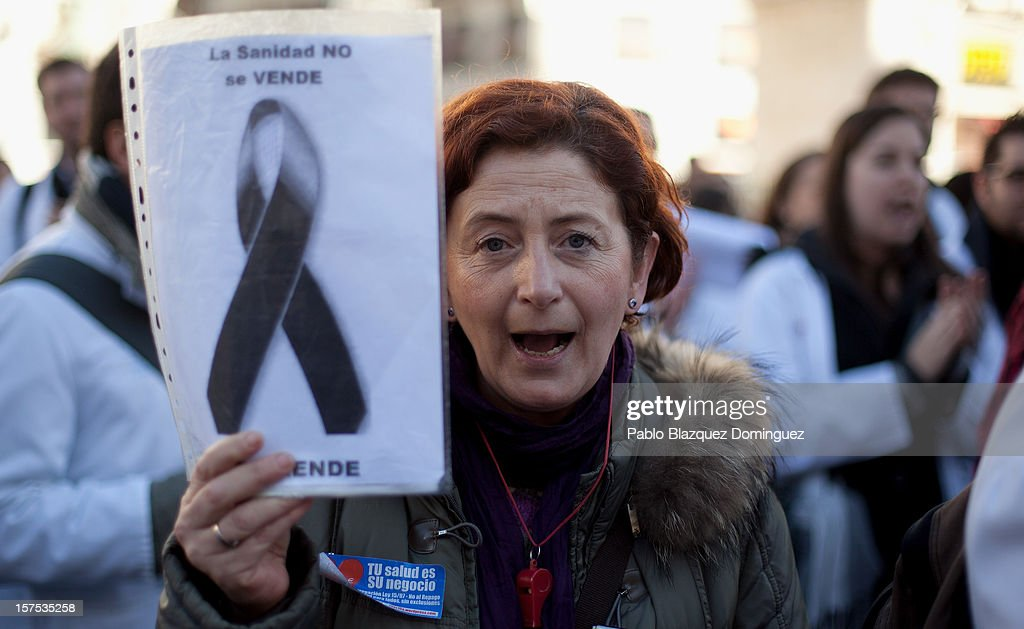 A woman shouts slogan and holds a placard reading 'Health service is not for sale' amid other health workers during a demonstration at Puerta del Sol Square on December 4, 2012 in Madrid, Spain. All trade unions called for the second 48 hours health workers' general strike in Madrid region, after Regional Government announced severe cuts and privatization of Medical Centers.