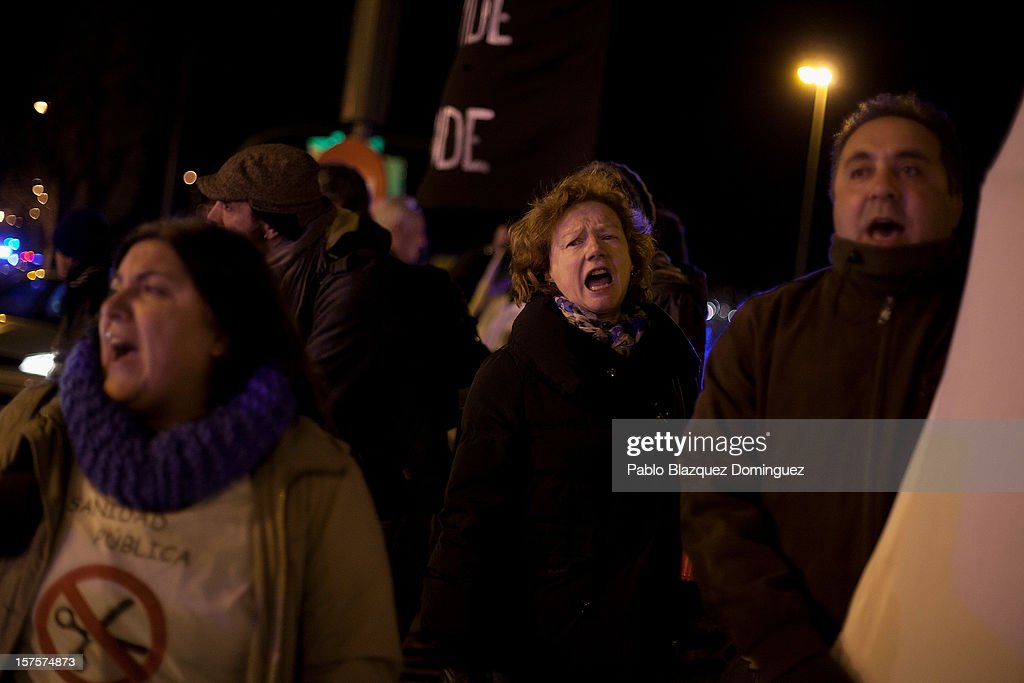 A woman shouts slogans amid other health workers during a demonstration at Puente de Toledo on December 4, 2012 in Madrid, Spain. All trade unions called for the second 48 hours health workers' general strike in Madrid region, after Regional Government announced severe cuts and privatization of Medical Centers.