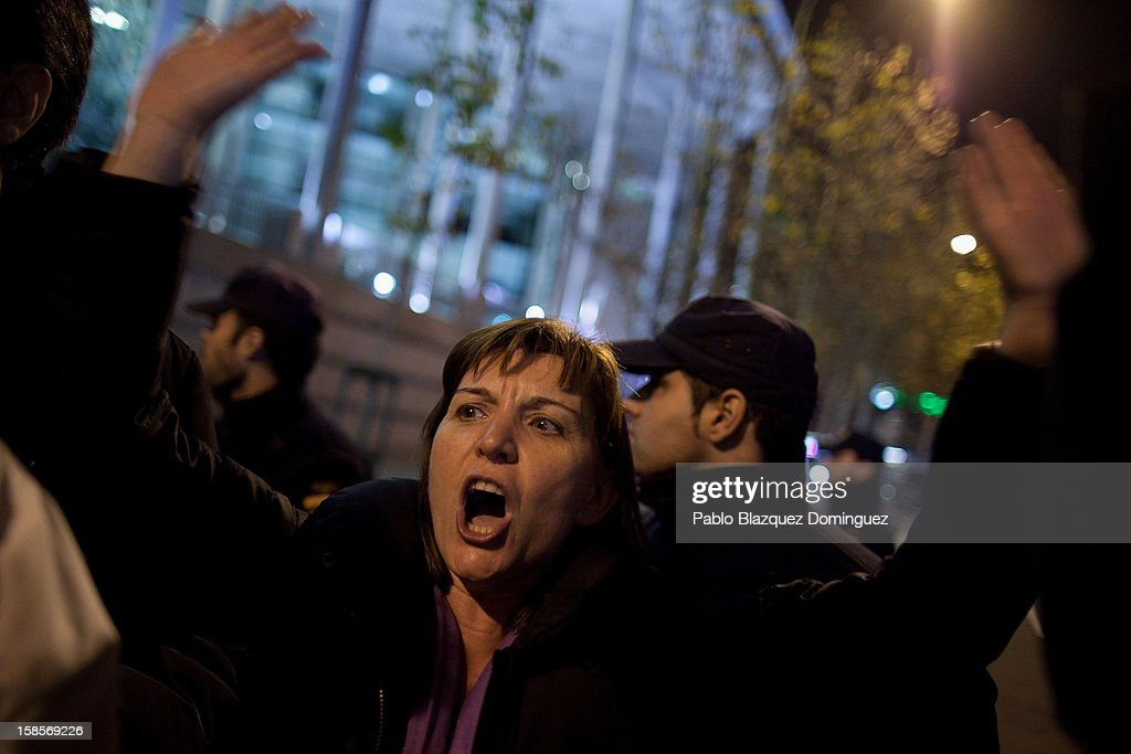 A woman shouts slogans amid other health workers during a demonstration outside Madrid Regional Asembly on December 19, 2012 in Madrid, Spain. As of today, health workers unions are calling for a third 48-hour strike against cuts on public health care and the privatization of medical centers and hospitals.