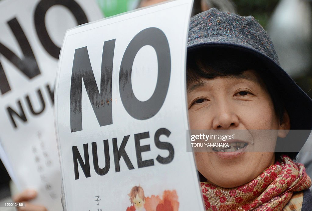 A woman shouts slogans as she holds a placard during a rally denoucing nuclear power plants in front of the Diet building in Tokyo on November 11, 2012. Several thousand people took part in the rally. AFP PHOTO/Toru YAMANAKA