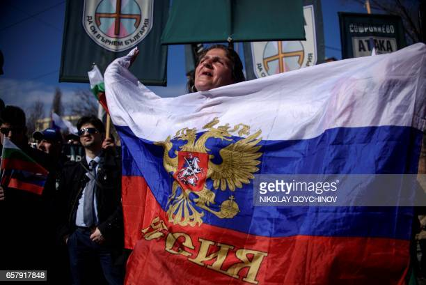 A woman shouts slogans as she holds a Russian flag during a political rally on Bulgaria's National Day in central Sofia on March 3 2017 Member of...
